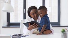 Medico che mostra il pc della compressa al paziente del bambino alla clinica stock footage