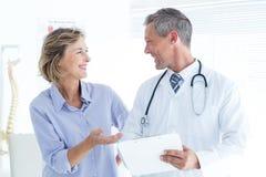 Medico che mostra le sue note al suo paziente fotografia stock