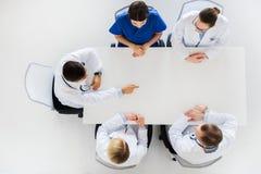 Medico che mostra qualche cosa di immaginario sulla tavola Immagine Stock Libera da Diritti