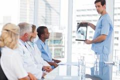Medico che mostra radiografia al suo gruppo Immagini Stock
