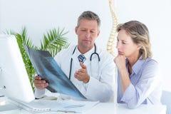 Medico che mostra raggi x al suo paziente Fotografia Stock Libera da Diritti