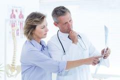 Medico che mostra raggi x al suo paziente Fotografia Stock