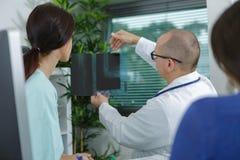 Medico che mostra risultato di radiologia all'apprendista Fotografia Stock