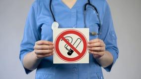 Medico che mostra segno non fumatori, specialista che avverte circa il danno di uso del tabacco immagine stock