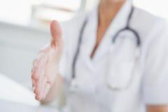 Medico che offre una mano alla scossa fotografie stock