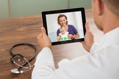 Medico che parla con paziente sopra video chiacchierata del computer portatile fotografia stock