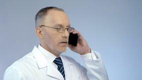 Medico che per mezzo del cellulare per organizzare riunione, controllante a distanza processo di trattamento Immagine Stock
