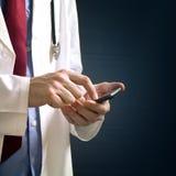 Medico che per mezzo dell'unità di smartphone Fotografia Stock