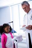 Medico che per mezzo della compressa digitale mentre misurando altezza della ragazza immagine stock libera da diritti