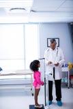 Medico che per mezzo della compressa digitale mentre misurando altezza della ragazza fotografia stock libera da diritti