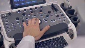 Medico che per mezzo della macchina di ultrasuono durante l'esame Attrezzatura diagnostica medica video d archivio