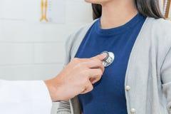 Medico che per mezzo dello stetoscopio al cuore ed ai polmoni dell'esame fotografia stock