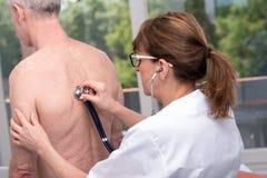 Medico che per mezzo dello stetoscopio al paziente dell'esame fotografia stock libera da diritti