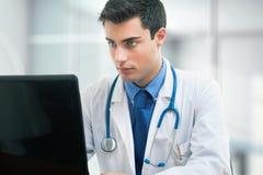 Medico che per mezzo di un computer portatile Immagine Stock Libera da Diritti