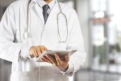 Medico che per mezzo di una compressa digitale Immagine Stock Libera da Diritti