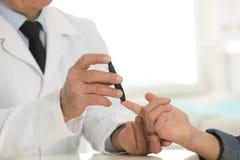 Medico che preleva il campione di sangue del paziente con la penna della lancetta in ospedale Controllo del diabete fotografie stock libere da diritti