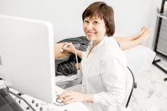 Medico che procede all'esame ecografico ad una giovane donna fotografia stock