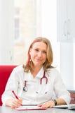 Medico che scrive prescrizione medica in chirurgia Fotografia Stock