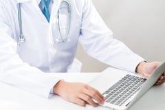 Medico che scrive su un computer portatile Immagini Stock