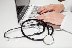 Medico che scrive sul computer portatile Fotografia Stock