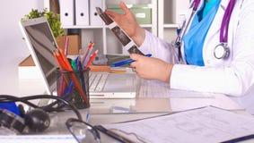 Medico che si siede alla tavola e che guarda i pazienti rontgen fotografia stock