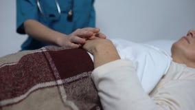 Medico che sostiene donna malato terminale, cura adeguata della gente nella casa di cura video d archivio