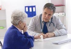 Medico che spiega diagnosi al suo anziano immagine stock