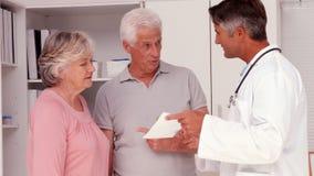 Medico che spiega prescrizione alle coppie anziane video d archivio