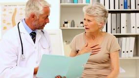 Medico che spiega una malattia al paziente video d archivio