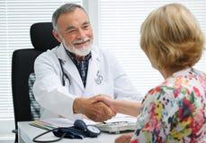 Medico che stringe le mani al paziente fotografie stock