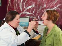 Medico che studia la gola del paziente Fotografie Stock Libere da Diritti