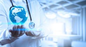 Medico che tiene un globo del mondo in sue mani Immagini Stock