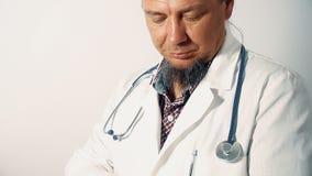 Medico che tiene una compressa digitale, esaminante la macchina fotografica, inclinazione