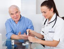 Medico che usando lancelet sull'uomo senior Immagini Stock