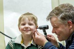 Medico che utilizza otoscopio nel giovane orecchio dei ragazzi Fotografie Stock Libere da Diritti