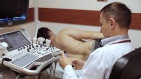 Medico clicca lo Smart Phone mentre sistema diagnostico di menzogne ed aspettante del paziente di ultrasuono video d archivio