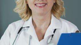 Medico con esperienza con la cartella della tenuta dello stetoscopio e sorridere nella macchina fotografica archivi video