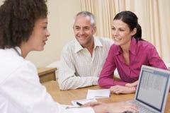 Medico con il computer portatile e le coppie nell'ufficio del medico Fotografie Stock Libere da Diritti