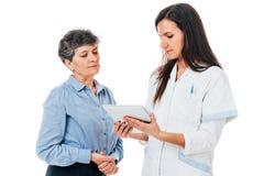 Medico con il cuscinetto sta spiegando il farmaco al paziente Fotografie Stock Libere da Diritti