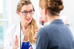 Medico con il paziente in un consulto immagini stock libere da diritti