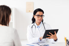 Medico con il pc e la donna della compressa all'ospedale Immagini Stock