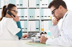 Medico con la compressa e l'infermiere al telefono in ufficio medico Fotografia Stock