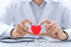 Medico con la mano dello stetoscopio che tiene forma rossa del cuore nell'ospedale fotografia stock libera da diritti