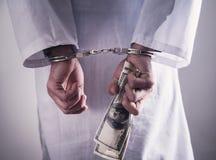 Medico con le manette ed i soldi Crimine medico fotografie stock libere da diritti