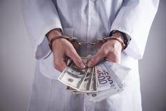 Medico con le manette ed i soldi Crimine medico fotografia stock
