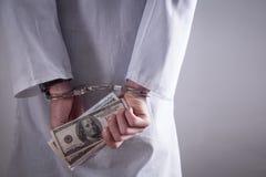 Medico con le manette ed i soldi Crimine medico fotografia stock libera da diritti
