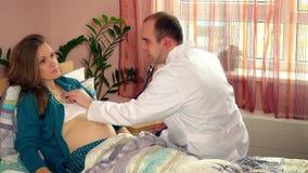 Medico con lo stetoscopio che controlla salute di giovane donna incinta che si trova a letto archivi video