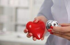 Medico con lo stetoscopio che esamina cuore rosso Fotografia Stock
