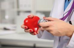 Medico con lo stetoscopio che esamina cuore rosso Fotografie Stock