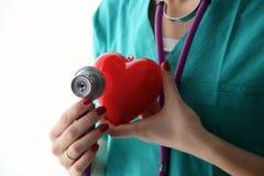 Medico con lo stetoscopio che esamina cuore rosso Fotografia Stock Libera da Diritti